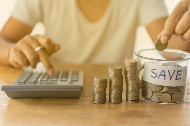 O empresário está colocando moedas na garrafa e acumulando na coluna que representam economia de dinheiro ou ideia de planejamento financeiro para a economia.
