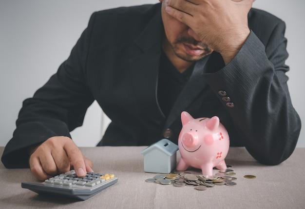 O empresário está estressado com a perda de seus empregos e com a falta de poupança para pagar uma hipoteca. foco na calculadora e impactos da epidemia de covid 19