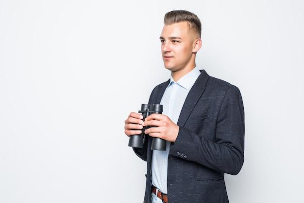 O empresário está olhando através de um par de binóculos isolado na parede branca