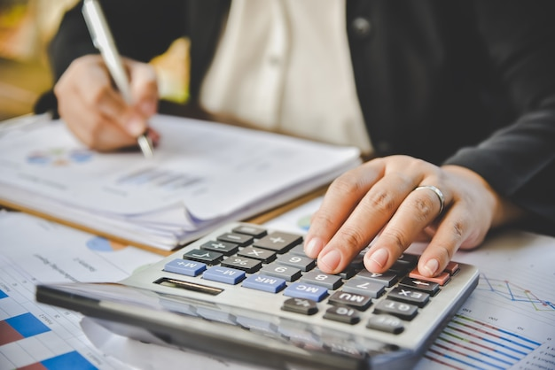 O empresário está trabalhando com uma calculadora e um documento.