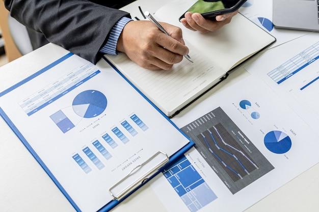 O empresário faz anotações do celular em um caderno, é dono da empresa, verifica os documentos financeiros da empresa em seu escritório. conceito de gestão financeira.