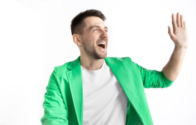 O empresário feliz em pé e sorrindo contra walll cinza.