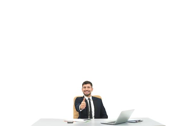 O empresário feliz na área de trabalho faz sinal de positivo sobre o fundo branco