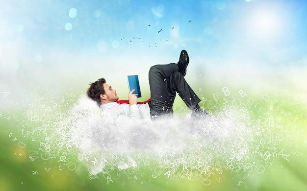O empresário lê um livro sobre uma nuvem macia de letras. conceito de relaxamento e imaginação
