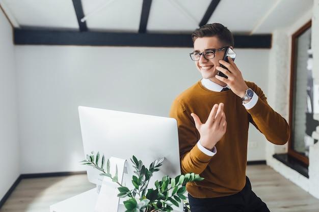 O empresário positivo com laptop e smartphone sempre tem acesso à internet.