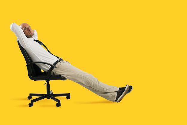 O empresário relaxa e pensa sentado em uma cadeira. fundo amarelo
