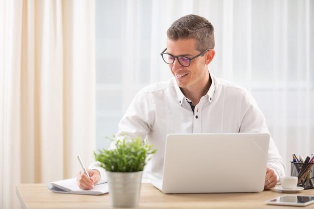 O empresário se senta em sua mesa atrás de seu caderno escrevendo notas, sorrindo.