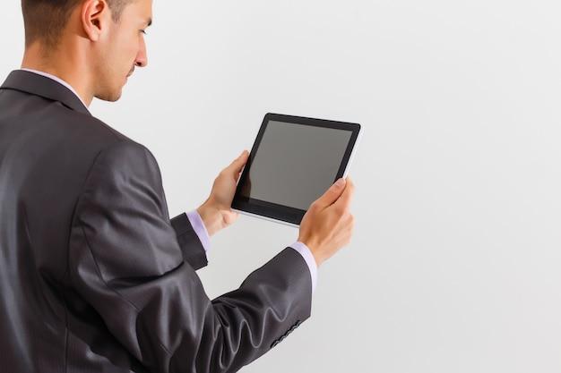 O empresário segurando o tablet contra um fundo branco