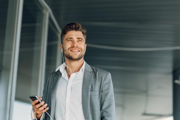 O empresário sorri e ouve música um jovem na rua com um telefone nas mãos