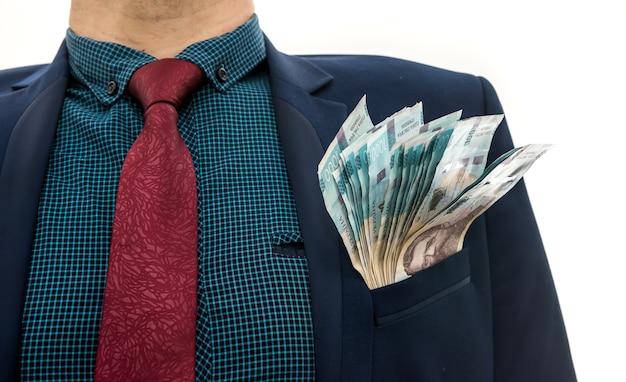 O empresário teve lucros enormes, mostrando muito dinheiro. um homem de terno segura um maço de banktons novos da ucrânia. 1000 hryvnia