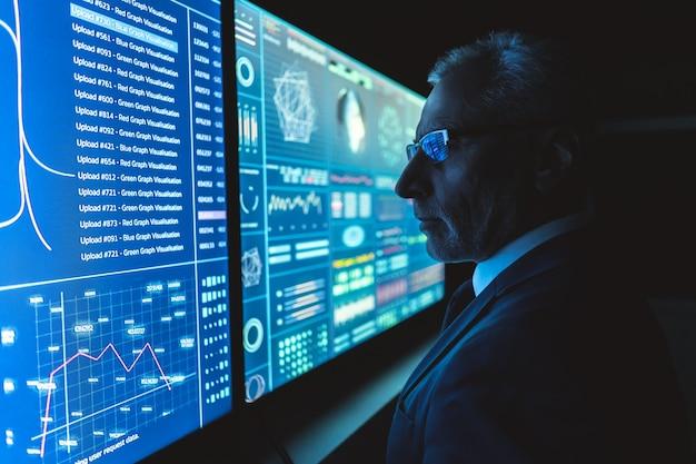 O empresário trabalha no grande visor do sensor no escritório escuro