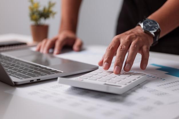 O empresário usa uma calculadora e um laptop para fazer finanças matemáticas em uma mesa branca em seu escritório