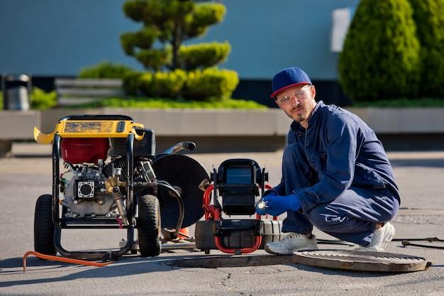 O encanador com câmera portátil para inspeção de tubos e outros trabalhos de encanamento.