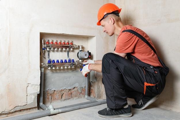 O encanador está fixando o coletor de distribuição no sistema de aquecimento do piso.