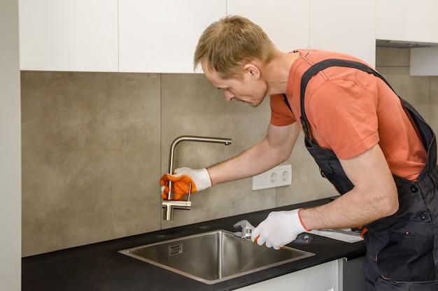 O encanador está instalando uma torneira na pia da cozinha.