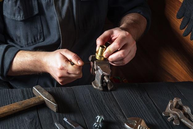 O encanador insere os acessórios de latão em um torno