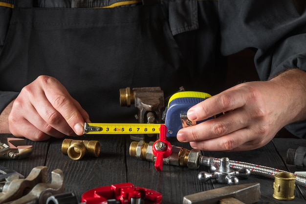 O encanador mestre mede a distância usando uma fita métrica. ambiente de trabalho em uma oficina com ferramentas e peças sobressalentes na mesa