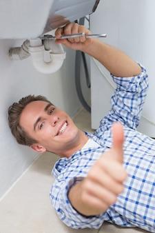 O encanador repara o dreno do lavatório enquanto gesticula o polegar para cima
