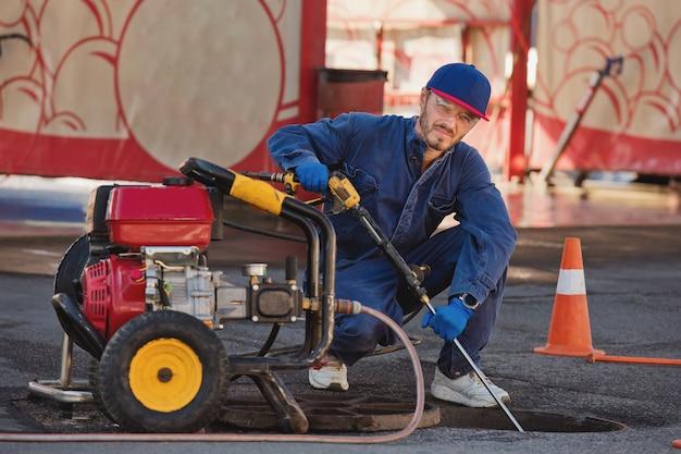 O encanador se prepara para consertar o problema no esgoto. trabalho de reparo na solução de problemas.
