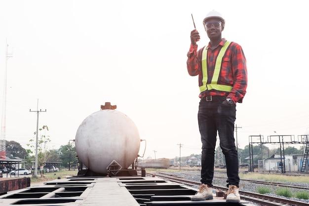 O engenheiro africano controla um trem na ferrovia falando por comunicação de rádio ou walkie talkie