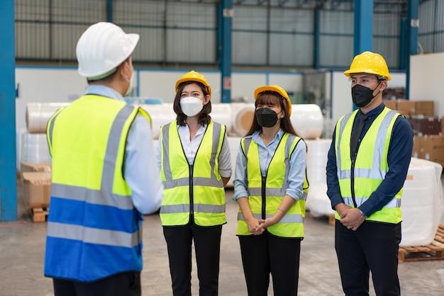 O engenheiro asiático do grupo usa máscara de proteção com capacete de segurança em pé, reunindo-se antes de trabalhar na fábrica