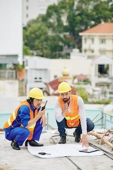 O engenheiro chefe verifica o plano de construção quando o empreiteiro controla o trabalho dos construtores por meio de um walkie-talkie