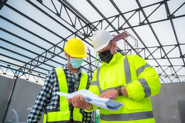 O engenheiro civil inspeciona a estrutura no canteiro de obras em relação ao projeto, os inspetores de construção inspecionam em conjunto a estrutura do edifício com o engenheiro civil. engenheiro civil segura planta inspecionar edifício.