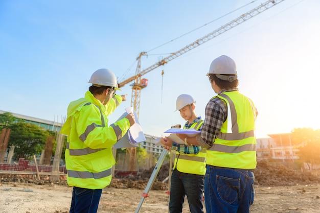 O engenheiro civil inspeciona o trabalho usando comunicação via rádio com a equipe de gerenciamento na área de construção.