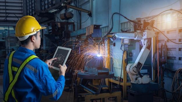 O engenheiro controla e verifica a robótica de soldagem automática de armas na fábrica inteligente