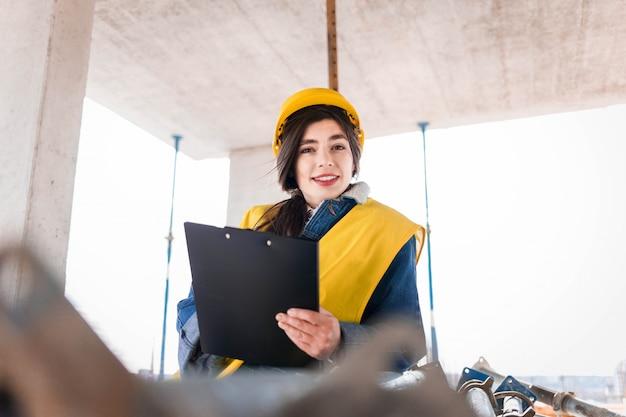 O engenheiro da moça em um capacete protetor enche o papel em uma construção