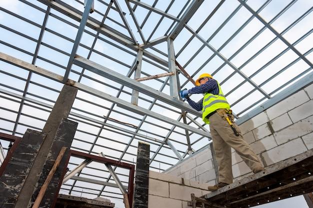 O engenheiro de construção está construindo a estrutura de telhado de aço da casa. conceito de construção de casa.