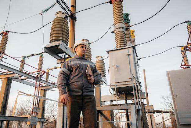 O engenheiro de energia inspeciona os equipamentos da subestação. engenharia de energia. indústria