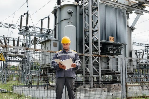 O engenheiro de energia inspeciona os equipamentos da subestação. engenharia de energia. indústria.