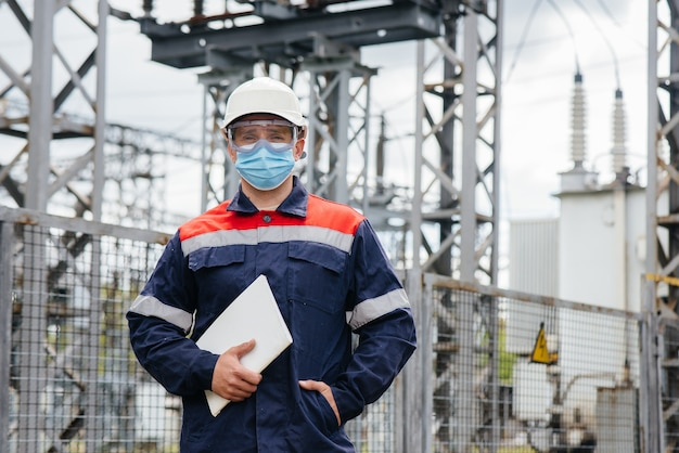 O engenheiro de energia inspeciona os equipamentos da subestação