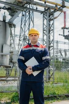 O engenheiro de energia inspeciona os equipamentos da subestação.