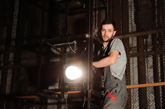 O engenheiro de iluminação ajusta as luzes no palco perto das cenas