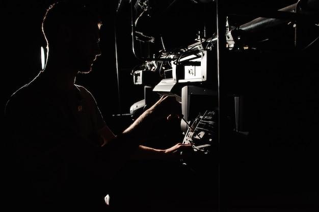 O engenheiro de iluminação repara o dispositivo de luz no palco