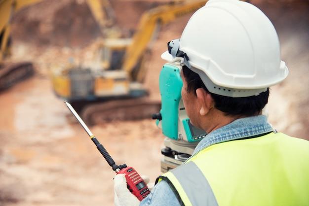 O engenheiro de pesquisa no canteiro de obras usa o teodolito que verifica trabalho de fundação de escavação
