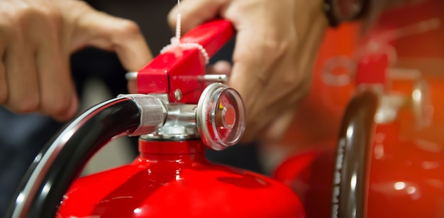 O engenheiro de proteção contra incêndio verifica o pino de segurança do tanque de extintores de incêndio vermelho