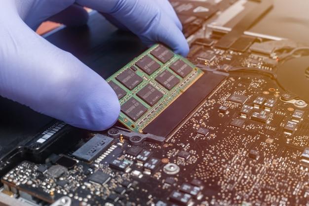 O engenheiro de serviço instala novos chips de memória ram no laptop