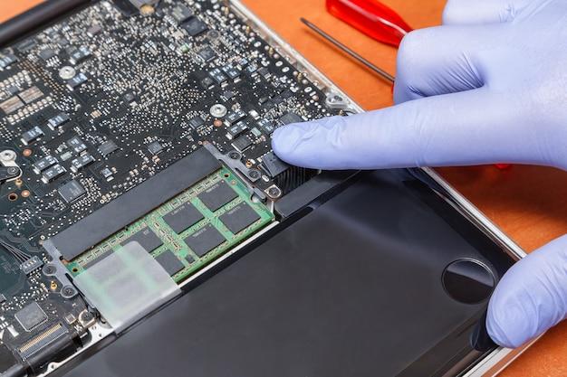 O engenheiro de serviço instala o plugue da bateria nova no laptop