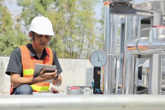 O engenheiro de sistema está verificando a pressão e gravando-a com um tablet.