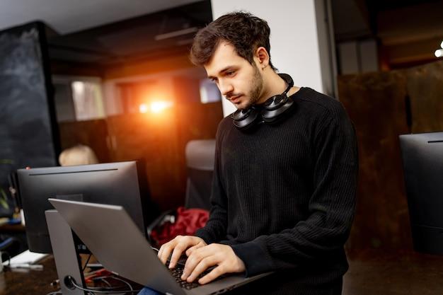 O engenheiro de software está sentado à mesa com o laptop nas mãos. escritório moderno em empresa de desenvolvimento