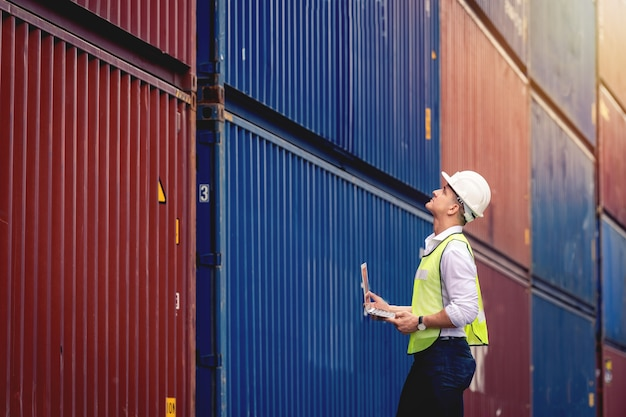O engenheiro de trabalho da portrit segura um laptop e caminha para verificar a caixa de contêineres do navio de carga para exportação e importação