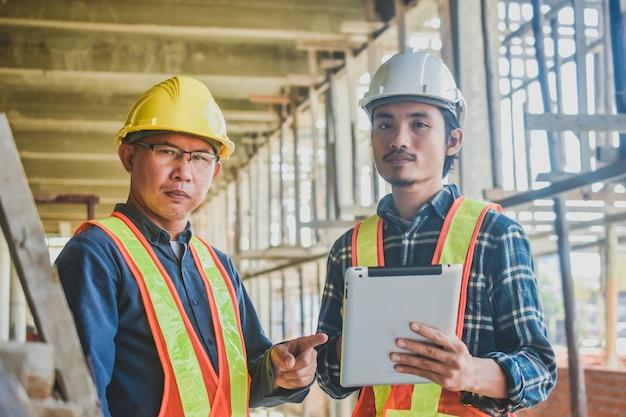 O engenheiro de trabalho em equipe usa um tablet na construção do local