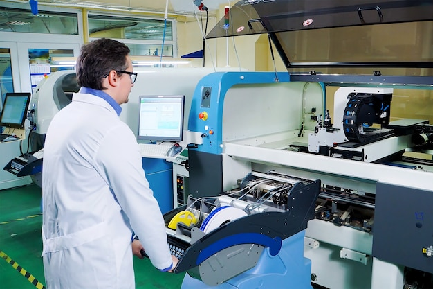 O engenheiro de túnica branca e óculos trabalha para a máquina surface mount technology.