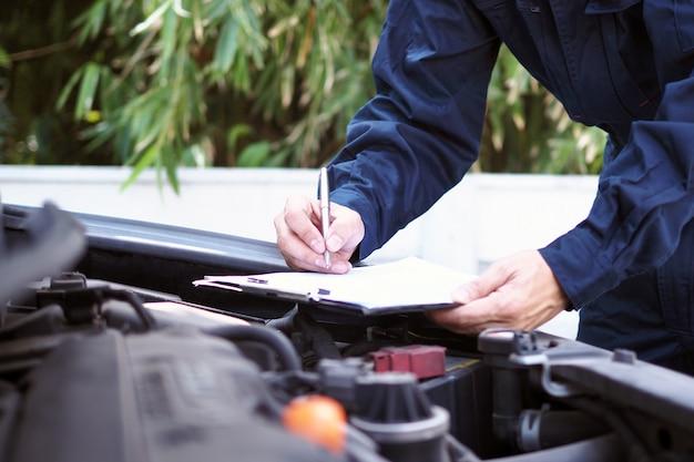 O engenheiro do motor está verificando e consertando o carro. serviços de cuidados fora do local