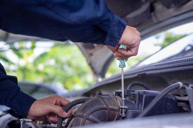 O engenheiro do motor está verificando e reparando o carro. serviços de atendimento externo