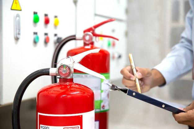 O engenheiro está verificando e inspecionando um extintor de incêndio vermelho na sala de controle de incêndio por segurança.
