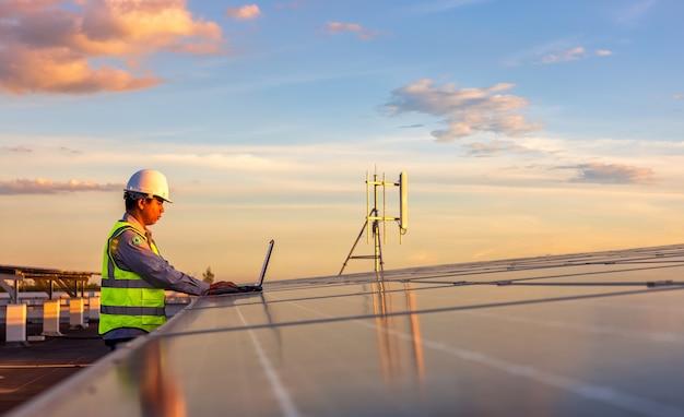 O engenheiro está verificando o sistema da estação de energia fotovoltaica de célula solar no telhado.